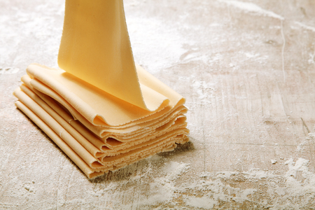 semolina pasta: Preparing Folded Fresh Egg Flat Pasta on Wooden Table Filled with Flour.