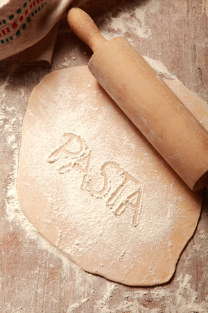 fussili: Homemade Flat Fresh Pasta Dough, Flattened by Wooden Roller, on Wooden Table Stock Photo