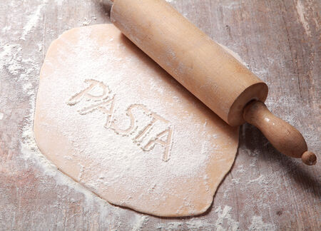 fussili: Close up Homemade Fresh Flattened Fettuccine Dough, Rolled by Wooden Dough Roller, Prepared on Wooden Table with Flour. Stock Photo