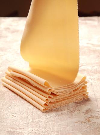 Close-up Verse Italiaanse Egg Flat pasta gemaakt door Pasta Roller op de Table Gevuld met Flour. Stockfoto