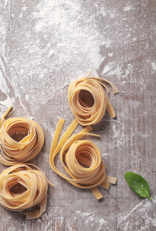 ribbon pasta: Rolled Fresh Italian Fettuccine Pasta on Wooden Table. Captured in Aerial View.