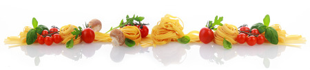 乾燥パスタや麺、トマト、バジル、装飾的な配置で新鮮なハーブを使用して行を持つ反射白い面の上のイタリア料理や食材のバナー 写真素材