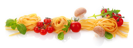Italian cooking and ingredients horizontal banner with dried pasta or noodles, cherry tomatoes, fresh basil and garlic cloves on a white background