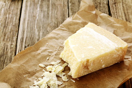 extensively: Wedge of parmigiano reggiano cheese, or parmesan, a hard granular regional cheese from Italy extensively used in Italain cuisine on rumpled brown paper with some grated to show texture