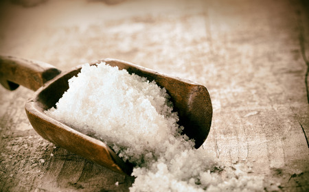 Coarse granules of natural rock or sea salt in a rustic old wooden ladle spilling out onto a grunge wooden table