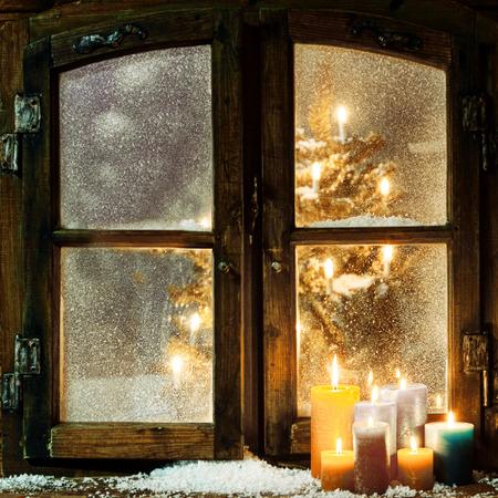 Gastvrije raam Kerstmis in een blokhut met een groep van brandende kaarsen op de vensterbank en een gloeiende kerstboom zichtbaar door de berijpte ruiten