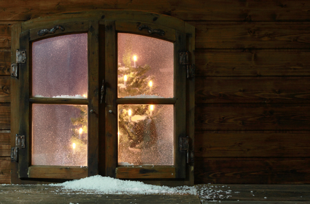 windows: Small Amount of Snow at Vintage Wooden Window Pane with Christmas Lights Inside the House.