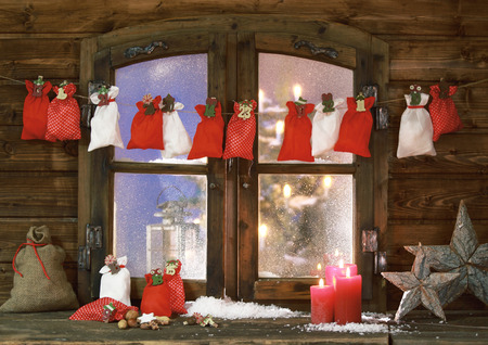 sachets: Small Christmas Sacks, Lighted Colored Candles and Stars at Vintage Wooden Window Pane Stock Photo