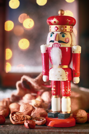 the nutcracker: Traditional colorful red Christmas wooden nutcracker in the figure of a king with assorted whole nuts in their shells in front of a window with a sparkling bokeh of party lights