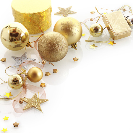 Stylish gold Christmas corner border with gifts, baubles, stars and ornaments over white with copyspace for your Xmas greeting photo
