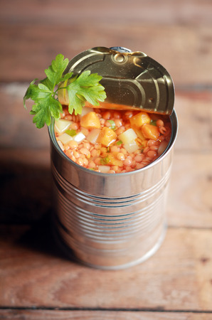 canned food: High angle view of an opened can of lentil and mixed vegetable soup garnished with fresh parsley for a delicious winter appetizer