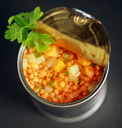 vegetable tin: Close up view from above of an opened tin of canned lentil and mixed vegetable soup with diced carrot and potato garnished with fresh parsley