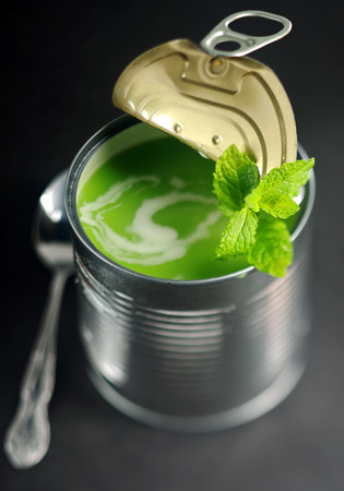 canned peas: Opened tin of fresh green pea soup garnished with a swirl of cream and fresh mint viewed from above with shallow dof