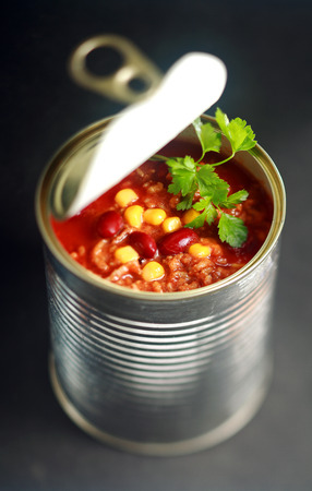 canned: Opened can of wholesome vegetable soup with sweetcorn, kidney beans and lentils garnished with fresh parsley viewed from above Stock Photo