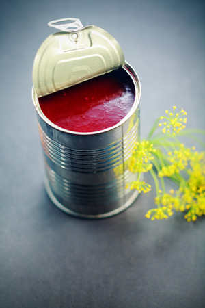 Close up Red Sauce Inside an Open Thin Can with Yellow Flowers on Side. Placed on Gray Platform. photo