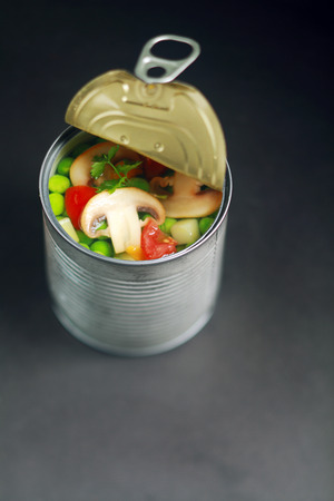 canned peas: Fresh Assorted Vegetables on Open Thin Can With No Label on Gray Table.
