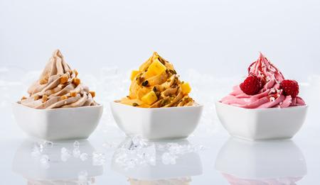 Yogures sabor Surtido delicioso congelados en pequeños tazones de fuente blancos aislados sobre fondo blanco Foto de archivo - 32820022