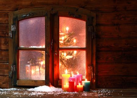 Kleine hoeveelheid sneeuw en Verlichte Gekleurde Kaarsen bij Vintage Ruit Tijdens Seizoen van Kerstmis. Stockfoto