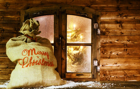 Full of Gifts Santa Sack at Vintage Wooden Window Pane During Christmas. photo
