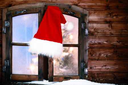 x country: Red and White Santa Hat Hanging at Rustic Window Pane with Small Amount of Snow During Christmas. Stock Photo