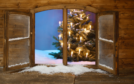Attractive View of Lighted Christmas Tree on Snow from Vintage Wooden Window Pane During Holidays. Stock Photo