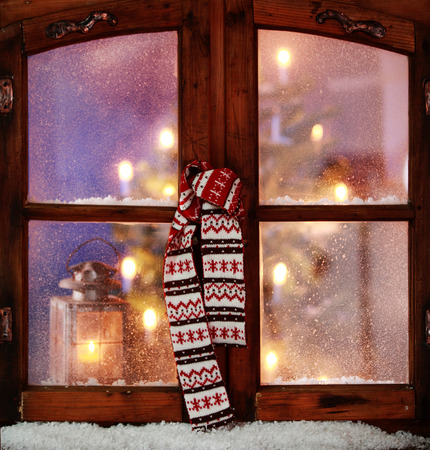 window pane: Close up Christmas Scarf Hanging on Vintage Wooden Window Pane with Small Amount of Snow.