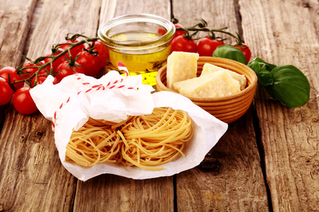 Fresh homemade pasta ingredients with egg noodles, parmigian reggiano cheese, olive oil, cherry tomatoes and basil on a rustic wooden kitchen counter photo
