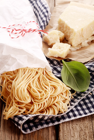 speciality: Preparing homemade Italian Pasta with fresh egg noodles, hard crumbly parmigiano reggiano speciality cheese and fresh basil on rustic wooden boards and a checked napkin