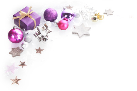 Colorful Christmas corner border over white with copyspace with silver, pink and purple star decorations and gift