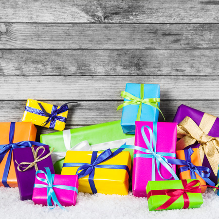 Close up Assorted Colored Christmas Gift Boxes with Ribbons on Snow with Wooden Wall . photo