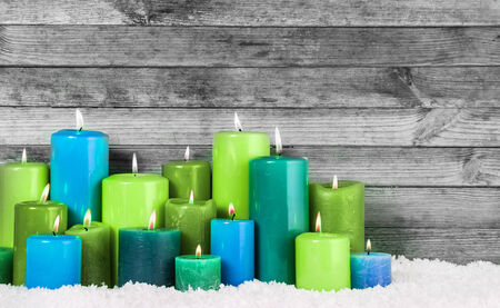 Close up Various Blue and Green Lighted Christmas Candles in Snow with Vintage Wall . photo
