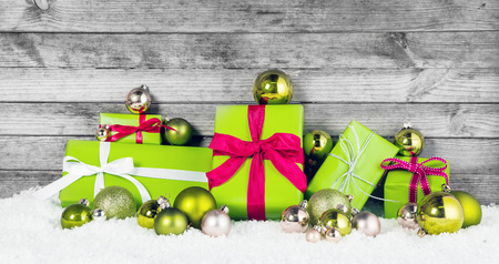 Close up Beautiful Apple Green Christmas Decorations with Assorted Size Presents and Balls on Snow. Display with Wooden . photo