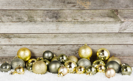 Close up Assorted Metallic Christmas Baubles For Decorations on the Snow with Wooden Wall . photo