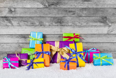 Close up Arranged Colored Christmas Gift Boxes with Ribbons on Man Made Snow with Gray Wooden Wall . photo