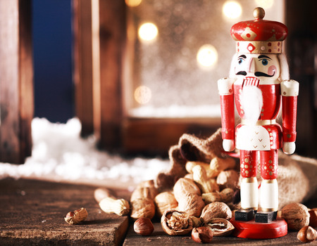 Close up Nutcracker Toy and Nuts on Wooden Table Near Window Pane. Captured on Christmas Holiday Season. photo