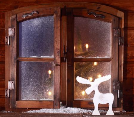 すりガラスの窓から見えるクリスマス ツリーの白熱灯の丸太小屋の素朴な窓辺にクリスマスを祝っているトナカイのデコレーション