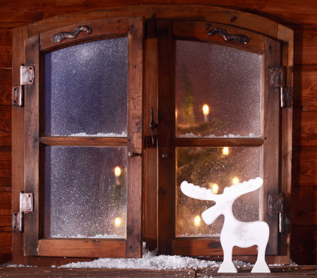 Reindeer decoration celebrating Xmas on a rustic windowsill of a log cabin with a glimpse of the glowing lights of a Christmas tree visible through the frosted window