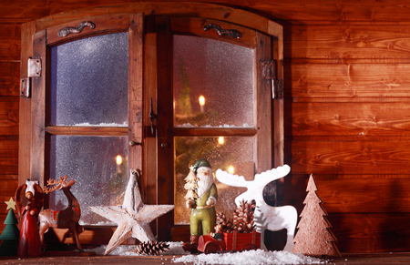 windowpanes: Festive Christmas log cabin window with a rustic collection of ornaments including reindeer, star, angel, Santa Claus and Christmas trees standing in the snow on the sill