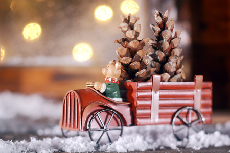 spoked: Piggy making a delivery of Xmas cones in a rustic vintage toy truck with metal spoked wheels driving through the snow on a windowsill with a bokeh of Christmas party lights behind Stock Photo