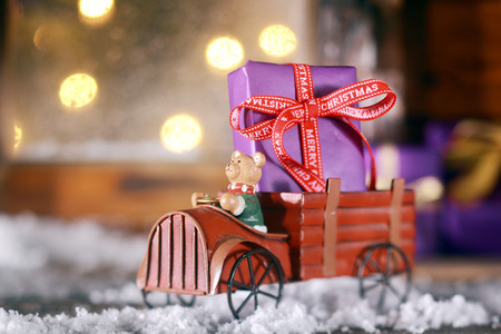 Cute rustic wooden toy truck with a Christmas gift in the back standing in the snow on the windowsill of a rustic wooden cabin with glowing party lights visible through the window photo