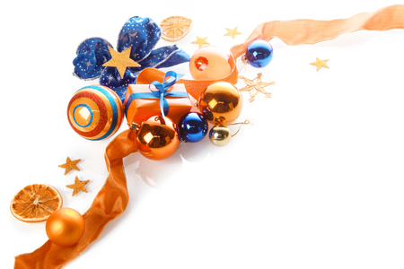 Colorful orange, gold and blue Xmas background over white with copyspace in a corner arrangement of baubles, ribbon, star, bow and gifts photo