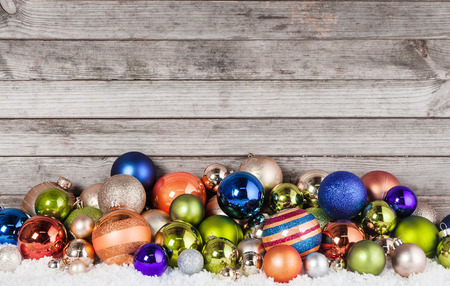 Close up Assorted Colored Christmas Balls Decorations on Snow with Vintage Wooden Wall Background. photo