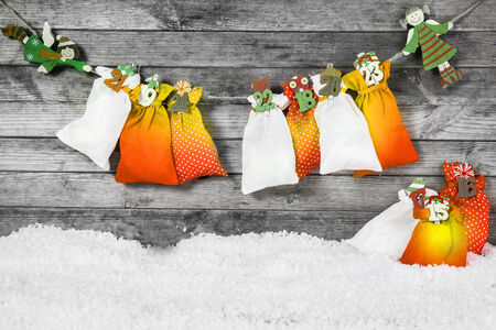 x country: Colored Santa Sacks and Man Made Snow for Christmas Decorations with Vintage Gray Wall Background.