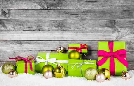 x country: Close up Attractive Green and Silver Christmas Decoration Items with Balls and Gift Boxes. Placed on Man Made Snow with Wooden Gray Wall Background.