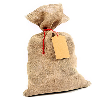 sackful: Rustic burlap sack tied with red string with a blank gift tag for your Christmas or seasonal greeting over white Stock Photo
