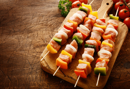 country kitchen: Tasty uncooked meat kebabs in a country kitchen with cubed meat, diced colorful bell peppers, onion and tomato on a wooden chopping board ready to grill on a wooden scored grungy counter top Stock Photo