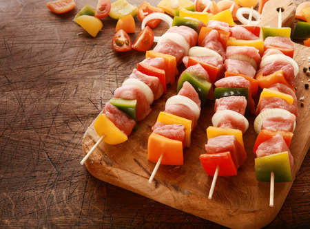 Delicious colorful meat and vegetable kebabs waiting to be cooked laid out ready on a wooden board on an old grungy table in a rustic kitchen, high angle view photo