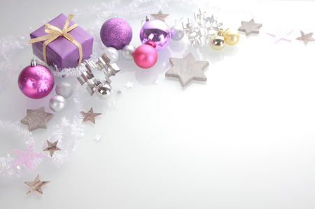 Christmas background with a decorative border of elegant silver, pink and purple stars, baubles, cookie cutters and a gift over white with copyspace Фото со стока