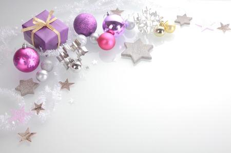 Navidad de fondo con un borde decorativo de plata elegante, rosa y estrellas púrpuras, chucherías, cortadores de galletas y un regalo más de blanco con copyspace