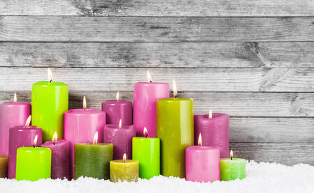 Close up Various Attractive Color Lighted Candles for Christmas Decoration on the Snow with Rustic Wooden Wall Background. photo
